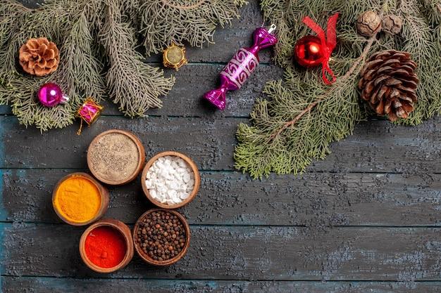 멀리 있는 크리스마스 트리 장난감에서 볼 수 있는 상위 뷰는 콘과 크리스마스 트리 장난감이 있는 나뭇가지 옆에 어두운 배경에 있는 향신료 5개