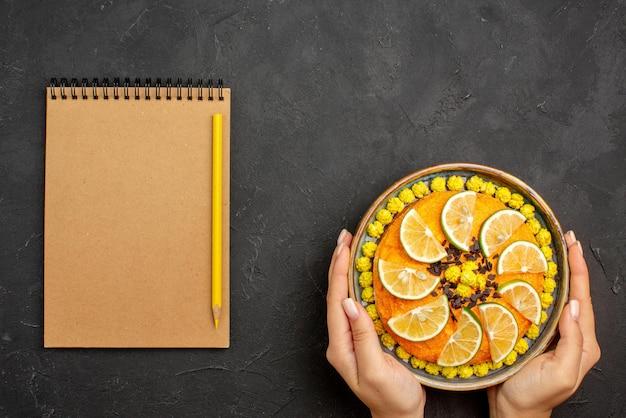 멀리 있는 감귤류 과일과 초콜릿 오렌지 케이크, 크림 공책 옆에 손에 초콜릿이 있고 검은 탁자에 노란색 연필이 있는 최고의 전망