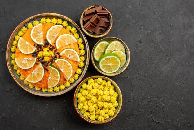 멀리 있는 감귤류 과일과 초콜릿 오렌지 케이크, 초콜릿 캔디 그릇 옆에 있는 초콜릿, 검은 탁자 위에 얇게 썬 라임이 있는 전망