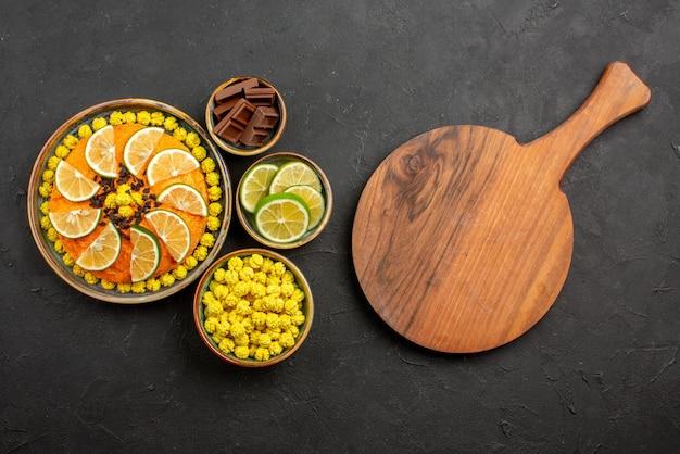 멀리 있는 감귤류 과일과 초콜릿 나무 커팅 보드에서 오렌지 케이크 옆에 초콜릿이 있는 초콜릿 캔디 그릇 옆에 있는 초콜릿과 검은색 테이블에 얇게 썬 라임이 있는 전망