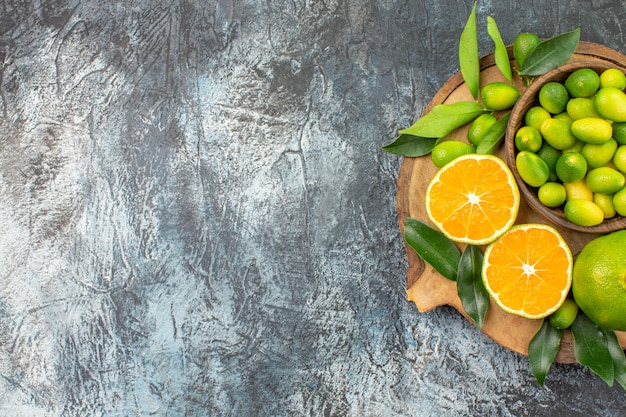 ボウルオレンジマンダリンに柑橘系の果物と遠くの柑橘系の果物ボードからの上面図 無料写真