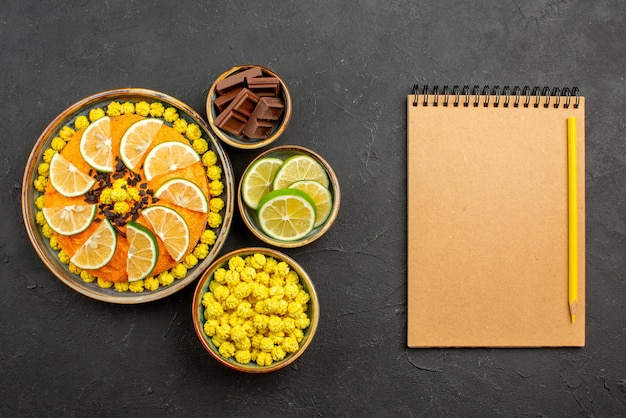 Top view from afar citrus fruits and chocolate orange cake with chocolate next to the bowls of candies chocolate and sliced limes next to the notebook and pencil on the black table