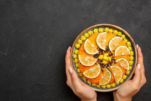 Vista dall'alto da lontano agrumi e torta al cioccolato e arancia con cioccolato nelle mani sul tavolo nero