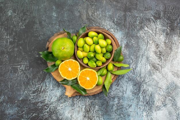 遠くの柑橘系の果物からの上面図ボード上に葉を持つさまざまな種類の柑橘系の果物