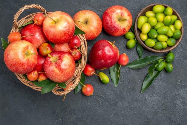 遠くからの上面図みかんりんごさくらんぼの葉と柑橘系の果物のボウル 無料写真