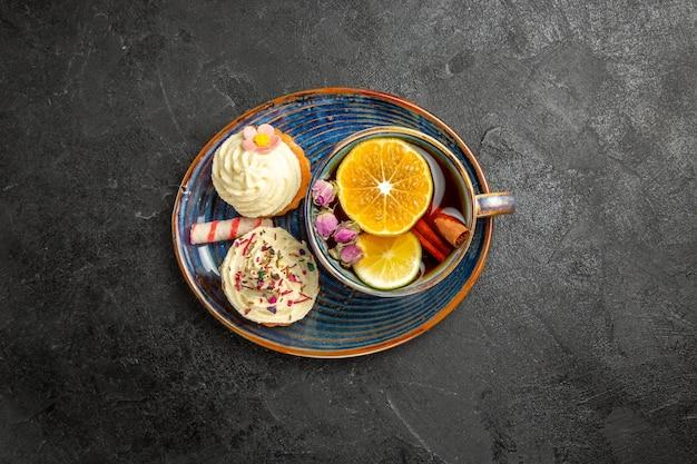 Vista dall'alto da lontano una tazza di tè al limone due cupcakes con panna e una tazza di tisana al limone sul piattino blu sul tavolo scuro