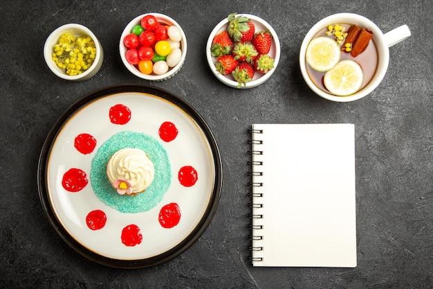 Vista dall'alto da lontano ciotole cupcake di dolci erbe e fragole accanto alla tazza di tisana quaderno bianco e piatto di appetitoso cupcake