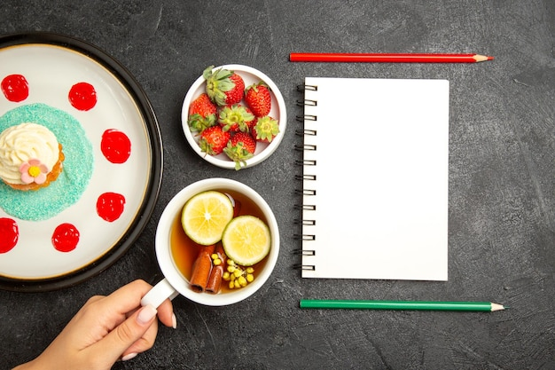 Top view from afar cupcake a cup of tea plate of cupcake bowl of strawberries next to the white notebook with two pencils and the cup of tea with lemon in hands