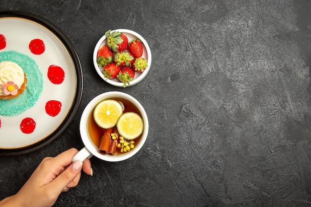 Vista dall'alto da lontano cupcake una tazza di tè piatto di cupcake una tazza di tè con bastoncini di cannella e limone in mano e ciotola di fragole