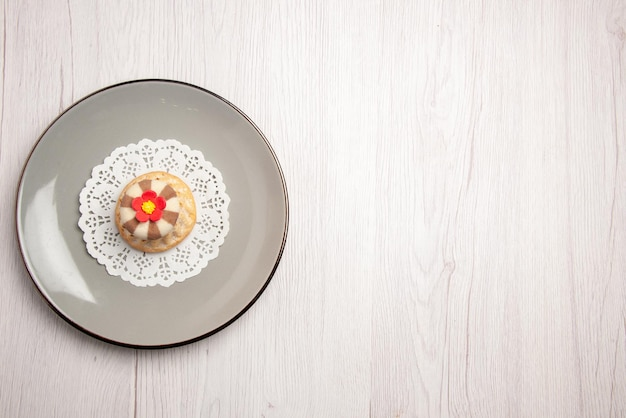 テーブルの左側にある白いレースのドイリーの遠くからのカップケーキカップケーキの上面図