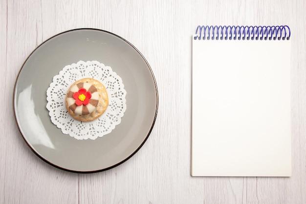 テーブルの上の白いノートの横にあるプレート上の白いレースのドイリーの遠くからのカップケーキカップケーキの上面図