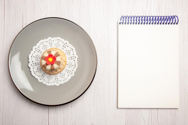 Vista dall'alto da lontano cupcake cupcake sul centrino di pizzo bianco sul piatto accanto al quaderno bianco sul tavolo