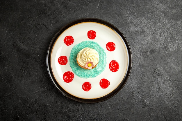 プレート上の遠くのカップケーキからの上面図暗いテーブルの中央にある白いプレートにソースがかかったカップケーキ