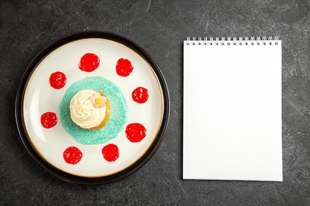 어두운 탁자에 있는 흰색 접시에 소스가 있는 컵케이크 옆에 있는 접시 흰색 공책에 있는 멀리 있는 컵케이크의 꼭대기
