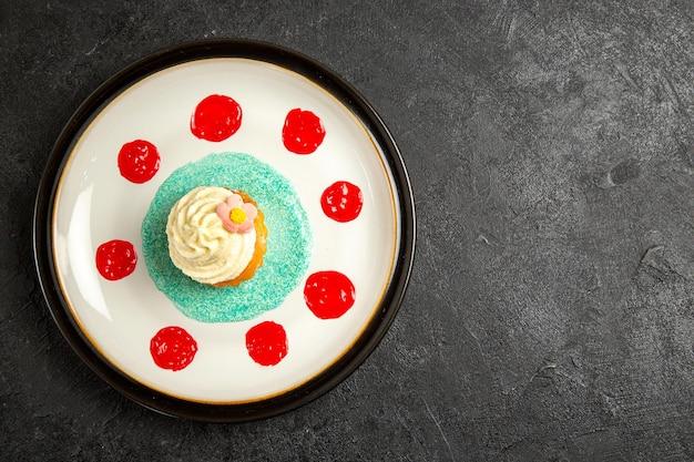 어두운 테이블의 왼쪽에 있는 컵케이크와 소스의 접시 흰색 접시에 있는 멀리 컵케이크에서 상위 뷰