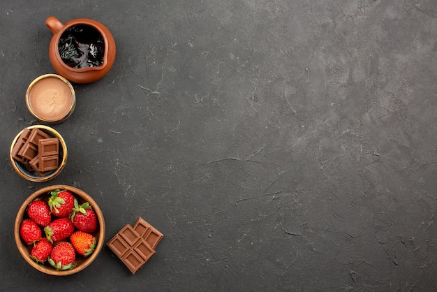 Vista dall'alto da lontano dessert crema al cioccolato in una ciotola fragole e barrette di cioccolato sul lato sinistro del tavolo scuro