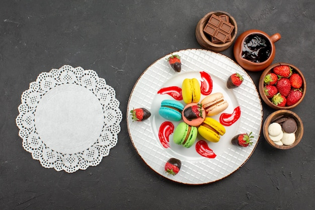 Top view from afar dessert macaroons and strawberries in the plate next to the lace doily and bowls with chocolate strawberries and chocolate cream on the table