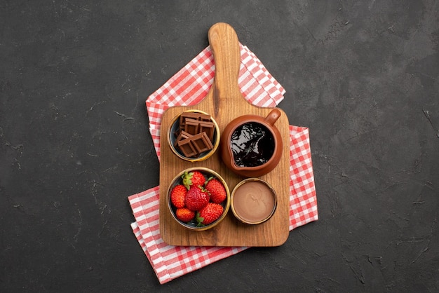 어두운 탁자에 있는 분홍색 흰색 체크 식탁보에 있는 도마에 식욕을 돋우는 초콜릿 크림과 딸기가 있는 식탁보 그릇에 있는 멀리 있는 디저트의 꼭대기