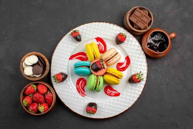 テーブルの上のチョコレートイチゴとチョコレートクリームのボウルの間にフランスのマカロンとイチゴの遠くのデザートプレートからの上面図