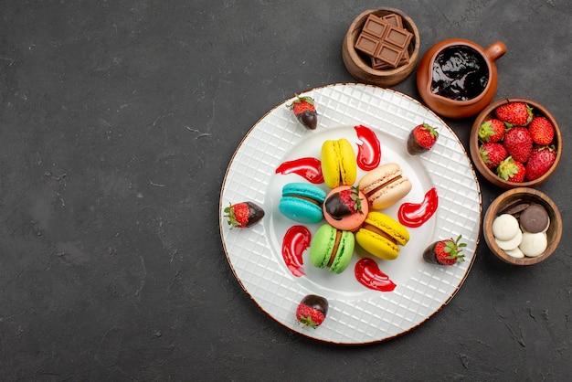 テーブルの右側にチョコレートイチゴとチョコレートクリームが付いているボウルの横にある遠くのデザートおいしいマカロンとイチゴからの上面図
