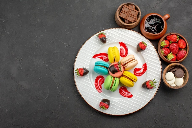 Vista dall'alto da lontano dessert gustosi amaretti e fragole accanto alle ciotole con fragole al cioccolato e crema al cioccolato sul lato destro del tavolo