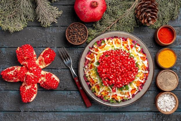 어두운 탁자에 원뿔이 있는 향신료 포크와 나무 가지 옆에 있는 식욕을 돋우는 석류 접시와 나무 가지의 꼭대기 전망