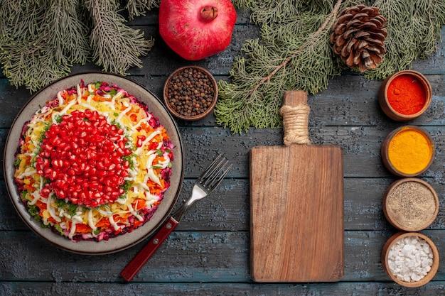 スパイスのまな板ボウルの横にあるザクロの種子の遠い皿と木の枝の皿からの上面図ザクロのフォークと木の枝の円錐形