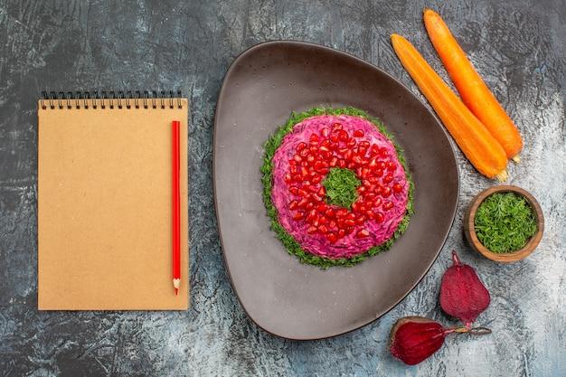 Vista dall'alto da lontano piatto un appetitoso piatto erbe taccuino matita carote barbabietole