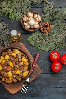 Top view from afar dish and branches dish of potatoes and mushrooms on the cutting board next to the fork and three tomatoes under oil bowl of white mushrooms and spruce branches