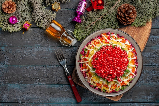 원뿔과 크리스마스 트리 장난감이 있는 나무 가지와 기름 포크 병 옆에 있는 커팅 보드에 석류 당근이 있는 접시 접시에 있는 멀리 있는 접시의 꼭대기