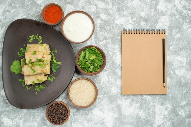 Vista dall'alto da lontano piatto in piatto cavolo ripieno con erbe in piatto accanto a spezie panna acida matita e taccuino marrone sul tavolo grigio