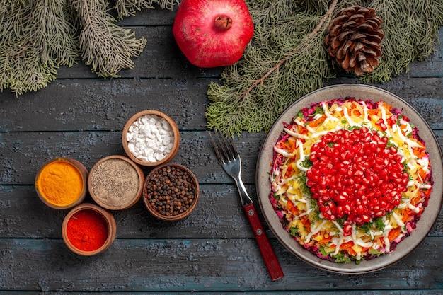 Vista dall'alto da lontano piatto e rami di albero ciotole di spezie forchetta melograno e rami di albero con coni accanto al piatto di appetitose carote e patate al melograno