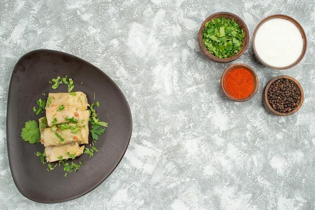 Vista dall'alto da lontano piatto con erbe piatto di cavolo ripieno accanto a ciotole con pepe nero panna acida erbe e spezie sul lato sinistro e destro del tavolo