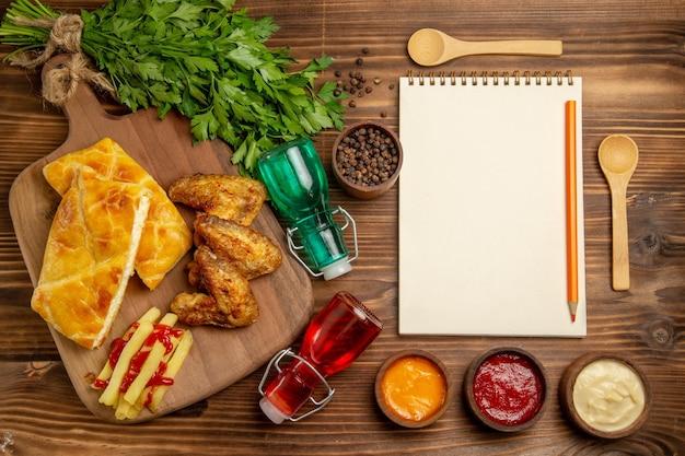 Vista dall'alto da lontano fastfood erbe patatine fritte pollo e torta sul tabellone accanto ai cucchiai spezie taccuino bianco matita bottiglie ed erbe aromatiche