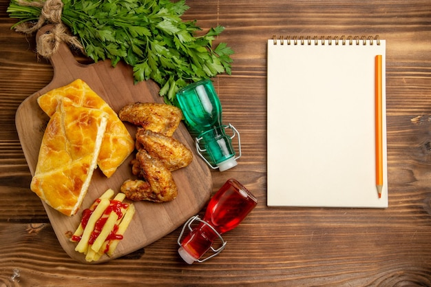 Top view from afar fastfood herbs french fries chicken and pieces of pie on the cutting board next to the white notebook pencil bottles and herbs