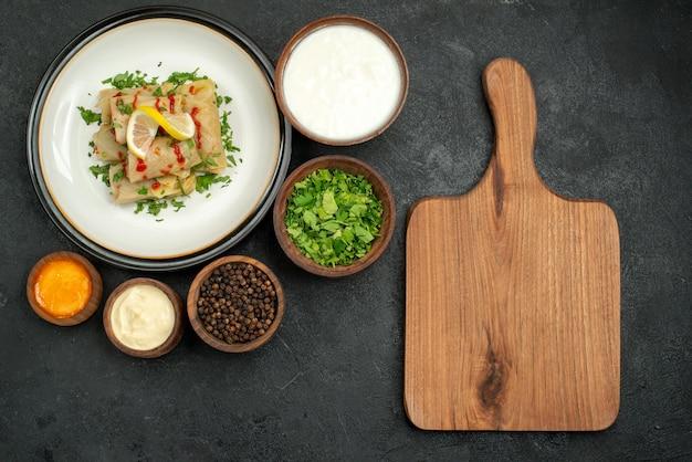 사워 크림 허브 블랙 페퍼, 노란색 소스, 허브 레몬과 소스를 곁들인 배추를 검은 탁자에 있는 나무 커팅 보드 옆에 있는 흰색 접시에 있는 테이블 그릇에 있는 멀리 있는 음식의 꼭대기