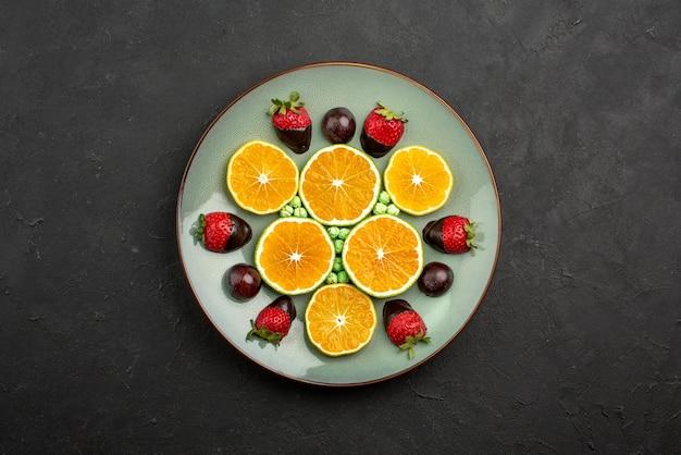 暗いテーブルの上にチョコレートで覆われたイチゴと緑のキャンディーと遠くの果物とチョコレートみじん切りオレンジからの上面図