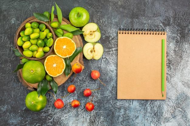 Vista dall'alto da lontano frutti i frutti di bosco appetitosi sul quaderno a matita di bordo