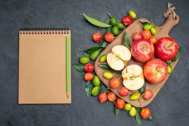Vista dall'alto da lontano frutti mele agrumi sul tagliere ciliegie matita notebook