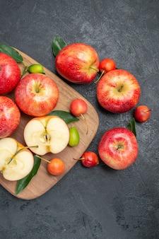 木の板に葉の果物とベリーと遠くの果物リンゴからの上面図