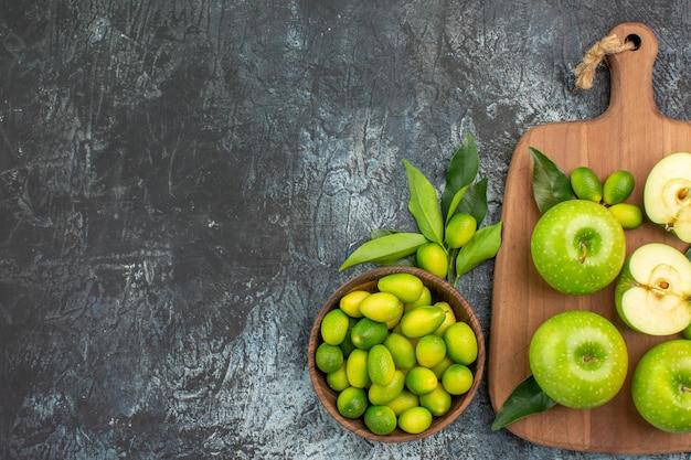 まな板の上に葉を持つ柑橘系の果物のリンゴの遠くのフルーツボウルからの上面図