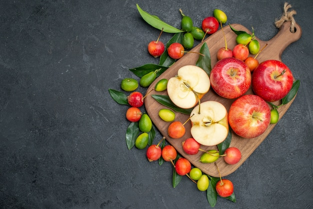 Вид сверху издалека плоды вишни вокруг яблок с листьями на разделочной доске