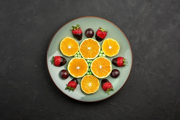 Vista dall'alto da lontano frutta e arancia tritata al cioccolato con fragole ricoperte di cioccolato e caramelle verdi sul tavolo scuro