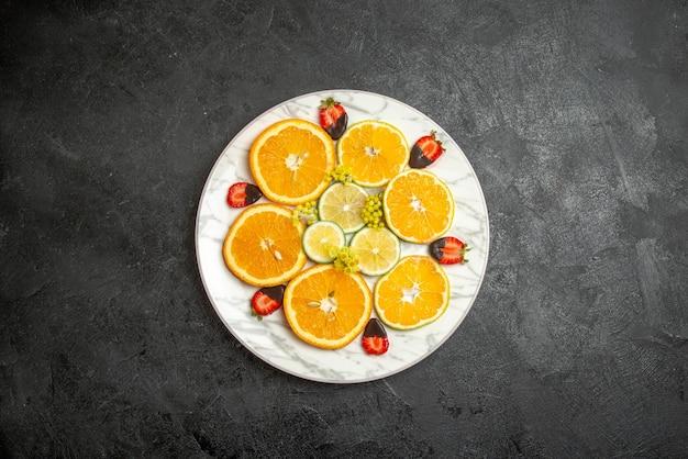 テーブルの中央にある白いプレートにスライスしたレモンオレンジとチョコレートで覆われたイチゴのプレート上の遠くの果物からの上面図