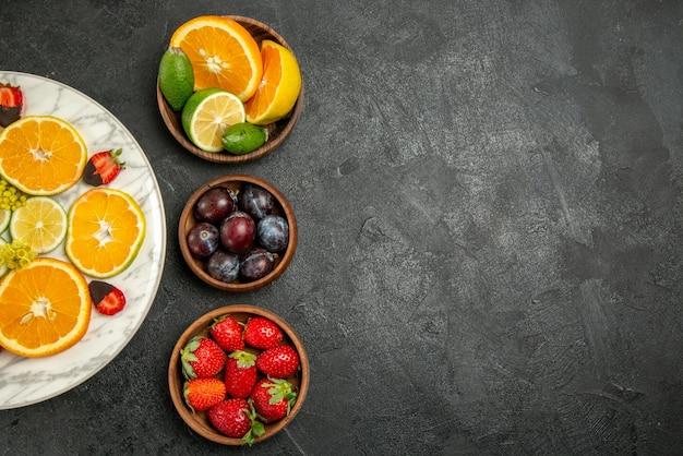 暗い表面の左側にあるベリーと柑橘系の果物のボウルの横にあるオレンジレモンとチョコレートで覆われたイチゴのテーブルプレート上の遠くの果物からの上面図