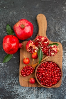 Top view from afar fruits pomegranate seeds spoon cherries pomegranate on the board