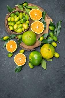 遠くの果物からの上面図暗いテーブル上のさまざまな柑橘系の果物のボード