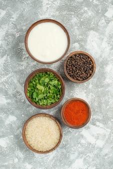 Vista dall'alto da lontano erbe spezie riso ciotola di erbe di riso panna acida spezie e pepe nero al centro del tavolo grigio