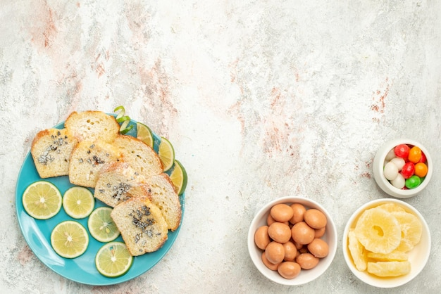 Top view from afar lemon bread white bread with herbs lemon in the plate next to bowls of candies on the table