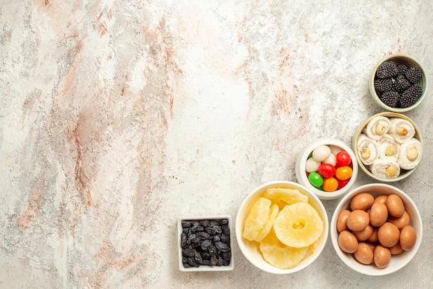 Vista dall'alto da lontano ciotole di torta al limone di caramelle appetitose sul lato destro del tavolo bianco